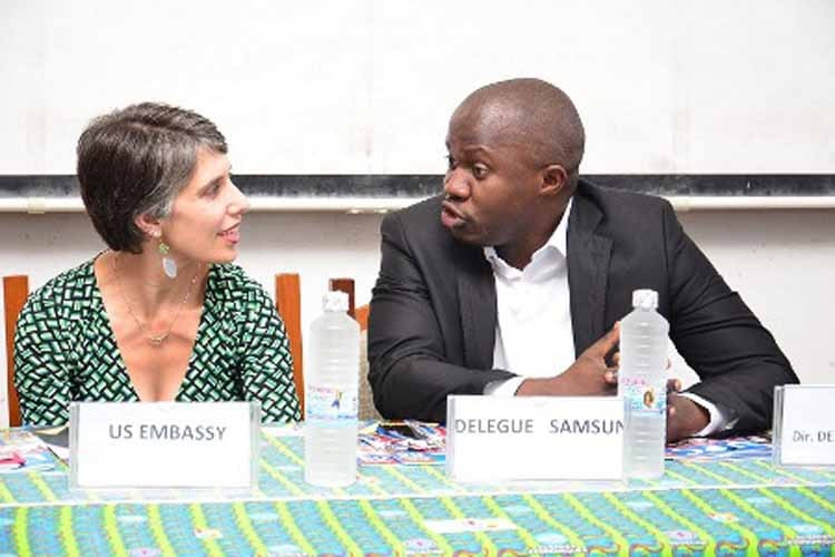 Mme Masi s'entretient avec le représentant de Samsung lors du lancement du magazine 'UPC Today'. (Images du Dépt. d'Etat)